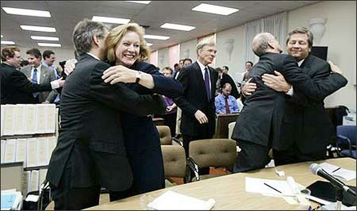 Lawyers for the Democratic Party hug after a judge upheld the election of Christine Gregoire. From left are Kevin Hamilton, Jenny Durkan, Russell Speidel, David McDonald and Dave Burman. Judge John Bridges denied Republicans' claims that election errors, illegal voters and fraud stole the election from GOP candidate Dino Rossi. (AP Photo/Elaine Thompson)