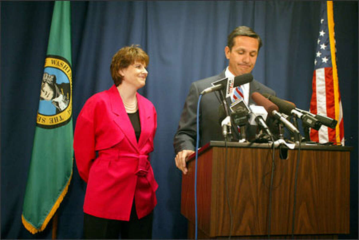 With his wife, Terry, at his side, Republican Dino Rossi announces at a Bellevue news conference that he won't appeal a ruling against him contesting the governor's race.