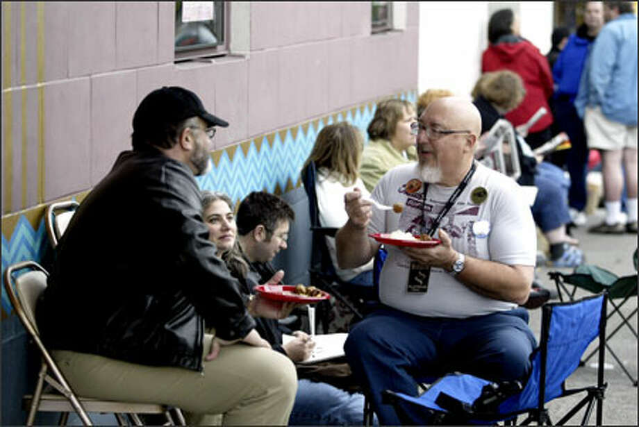 Christopher Conrad, left, and Steven Smith have lunch while in line at the Egyptian Theatre for the start of the Seattle International Film Festival. Photo: Jim Bryant/Seattle Post-Intelligencer / SEATTLE POST-INTELLIGENCER