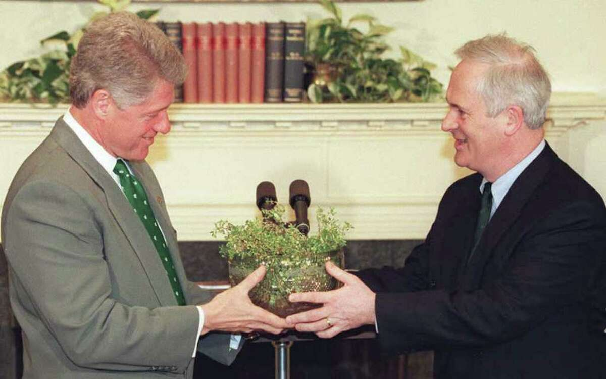 President Bill Clinton, left, receives a traditional St. Patrick's Day bowl of shamrocks from Irish Prime Minister John Bruton, right, at the White House on March 17, 1995.