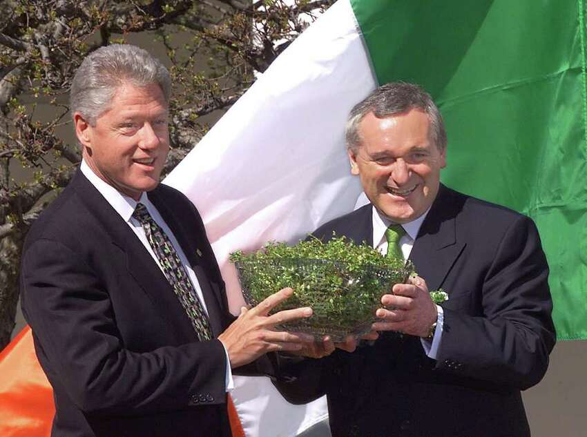 President Bill Clinton is presented a traditional bowl of shamrocks from Irish Prime Minister Bertie Ahern, right, on March 17, 1999 in the Rose Garden of the White House.
