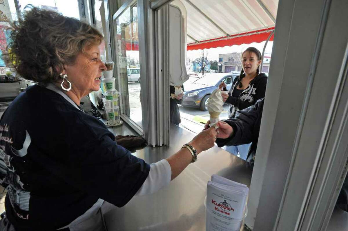 Kurver Kreme owner Lorie Meineker hands an ice cream cone to customer on opening day of the season in Colonie, NY, on March 17, 2011. Shannon Wright, age 16, of Valatie, eats her ice cream in the background. (Lori Van Buren / Times Union)