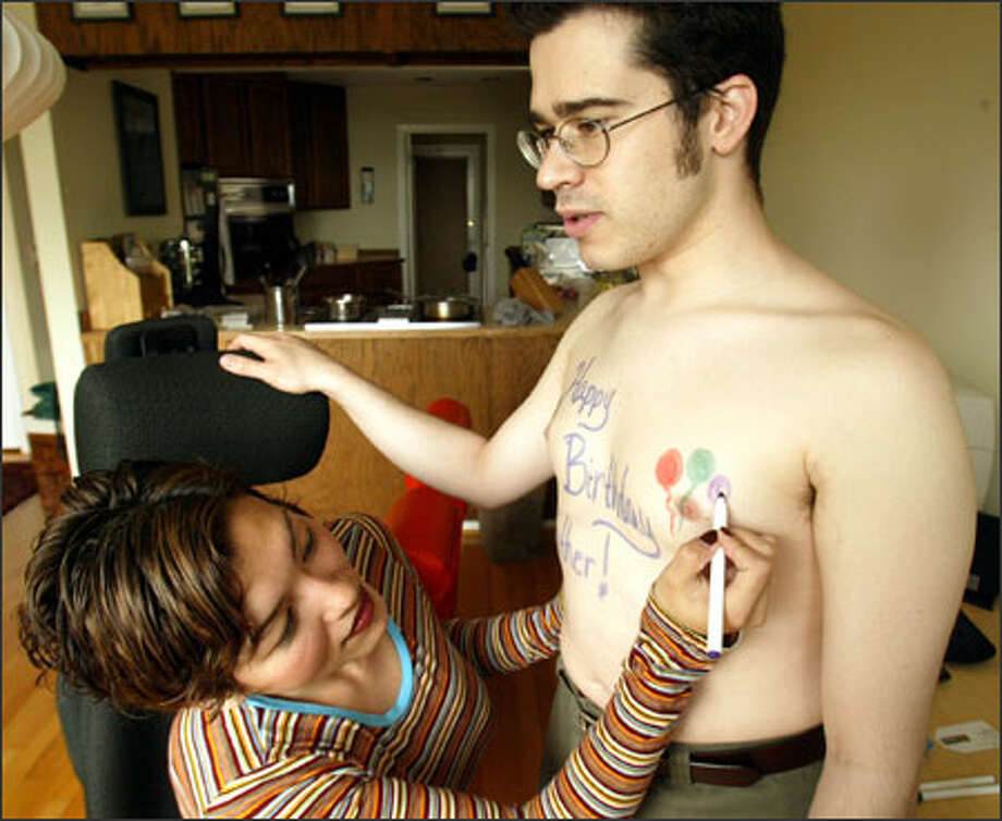 "Chris Pirillo's fiancee, ""Ponzi"" Indharasophang, draws a Father's Day greeting for her father on Pirillo's chest yesterday. Photo: Phil H. Webber/Seattle Post-Intelligencer"