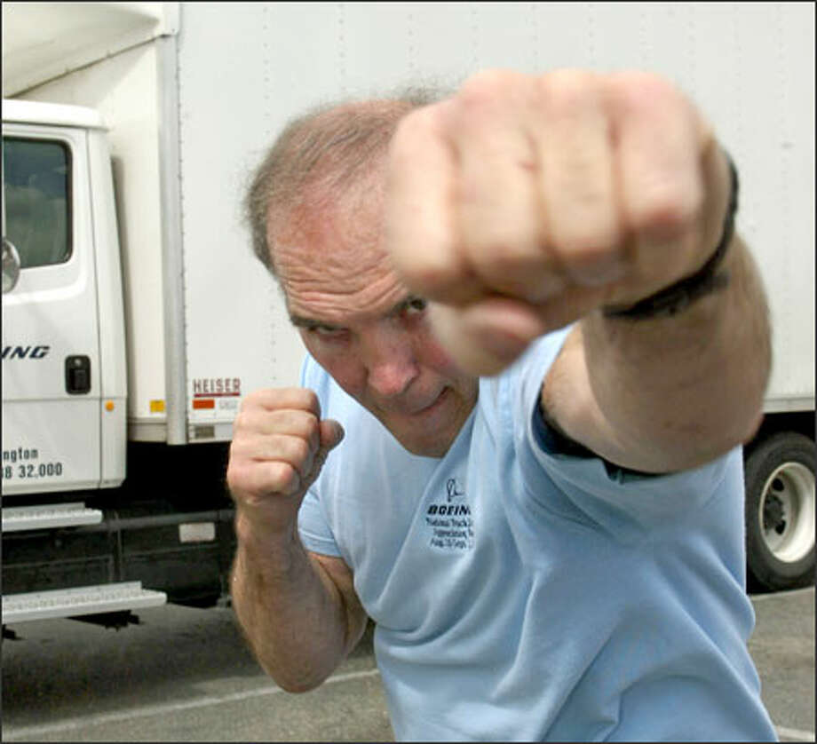 Boone Kirkman, 60, strikes a pose in front of the truck he drives for Boeing. It's been 27 years since the Renton native last electrified Northwest fans. Photo: Gilbert W. Arias/Seattle Post-Intelligencer / SEATTLE POST- INTELLIGENCER