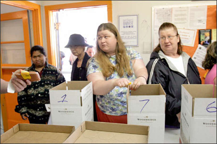 Stracy Fellers, center, and her mother, Cindy Allen, right, review a recent offering from the White Center Food Bank. The Fellerses haven't used food stamps since 1992. Photo: Meryl Schenker/Seattle Post-Intelligencer