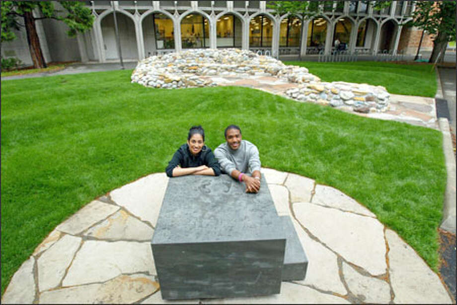 "Sumona Das Gupta, left, and Jaebadiah Gardner lean on the slave auction block of their sculpture ""Blocked Out,"" which honors those who are oppressed. Hear Gupta explain what the sculpture represents. Photo: Grant M. Haller/Seattle Post-Intelligencer"