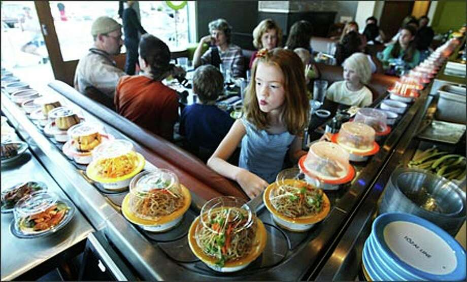 FILE -- The sushi goes round and round at Blue C Sushi; just grab what you want. Photo: Scott Eklund/Seattle Post-Intelligencer