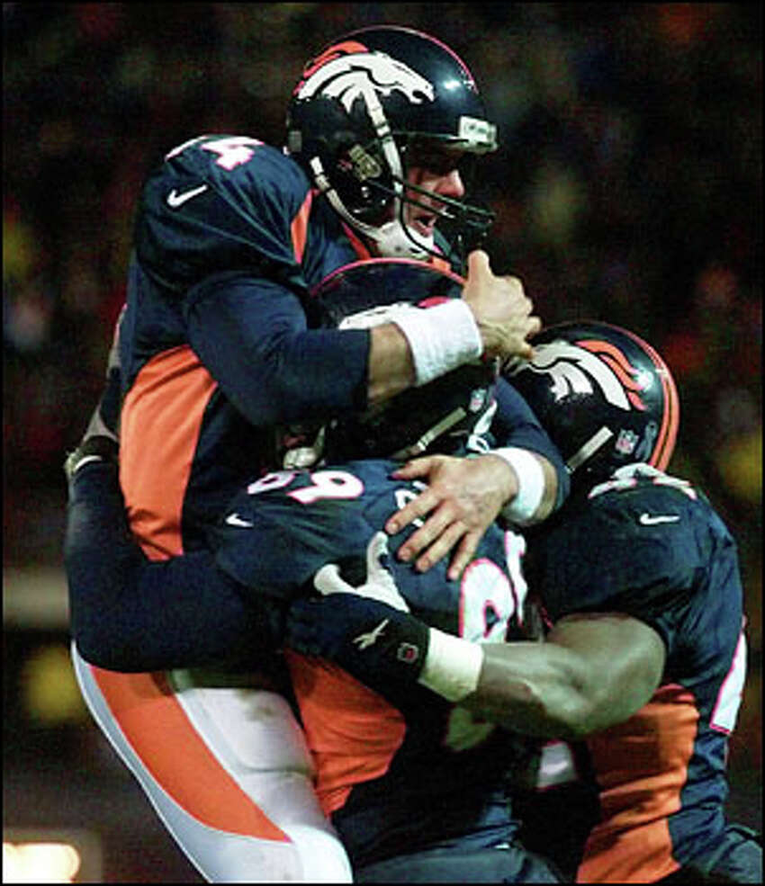 Broncos quarterback Brian Griese celebrates his touchdown pass to Dwayne Carswell with Carswell (89) and teammate Detron Smith.