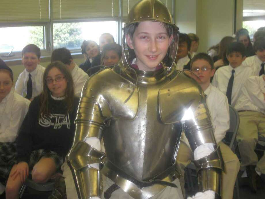 St. Thomas Aquinas School student Ryan Cimmino got to try on a suit of armor during a recent program on the Medieval ages at the school. Photo: Contributed Photo / Fairfield Citizen contributed
