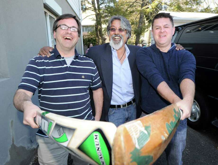 Greenwich residents from left, Frank Farricker, Sanjay Santhanam and Neil Kimberley, all members of the Mad Dogs Cricket Club of Greenwich, laugh as they pose with cricket bats at Santhanam's western Greenwich home Thursday afternoon, March 17, 2011, before heading out on a two-week trip to Sri Lanka to play cricket and watch some of the Cricket World Cup that is taking place there. Photo: Bob Luckey / Greenwich Time