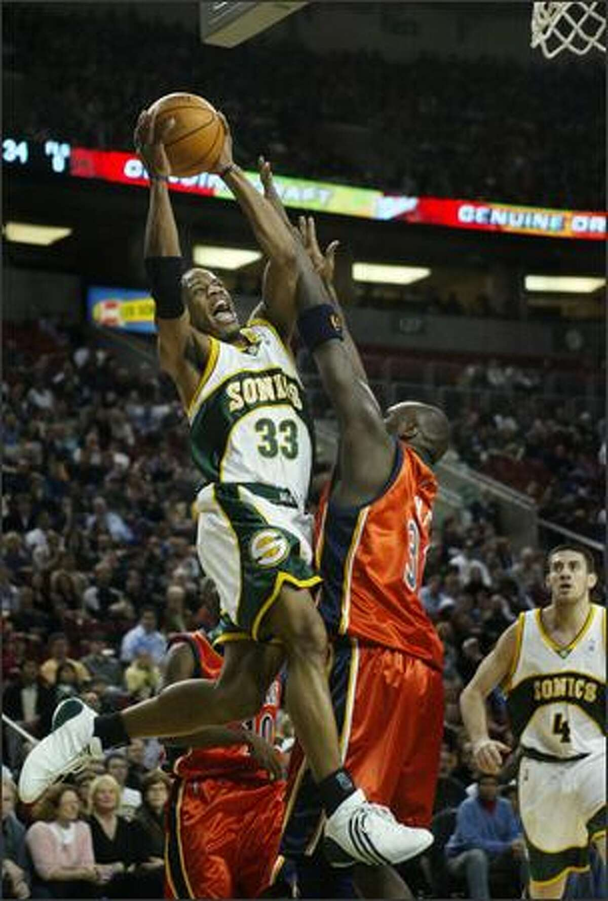 Sonics guard Antonio Daniels gets past Golden State's Adonal Foyle to score during the first half.
