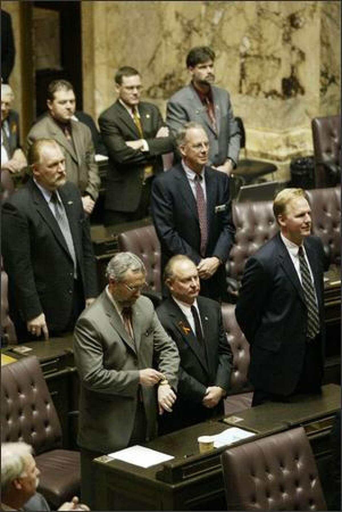 Republican members of the House and Senate, one looking at his watch, refused to applaud Christine Gregoire after she was sworn in as governor.