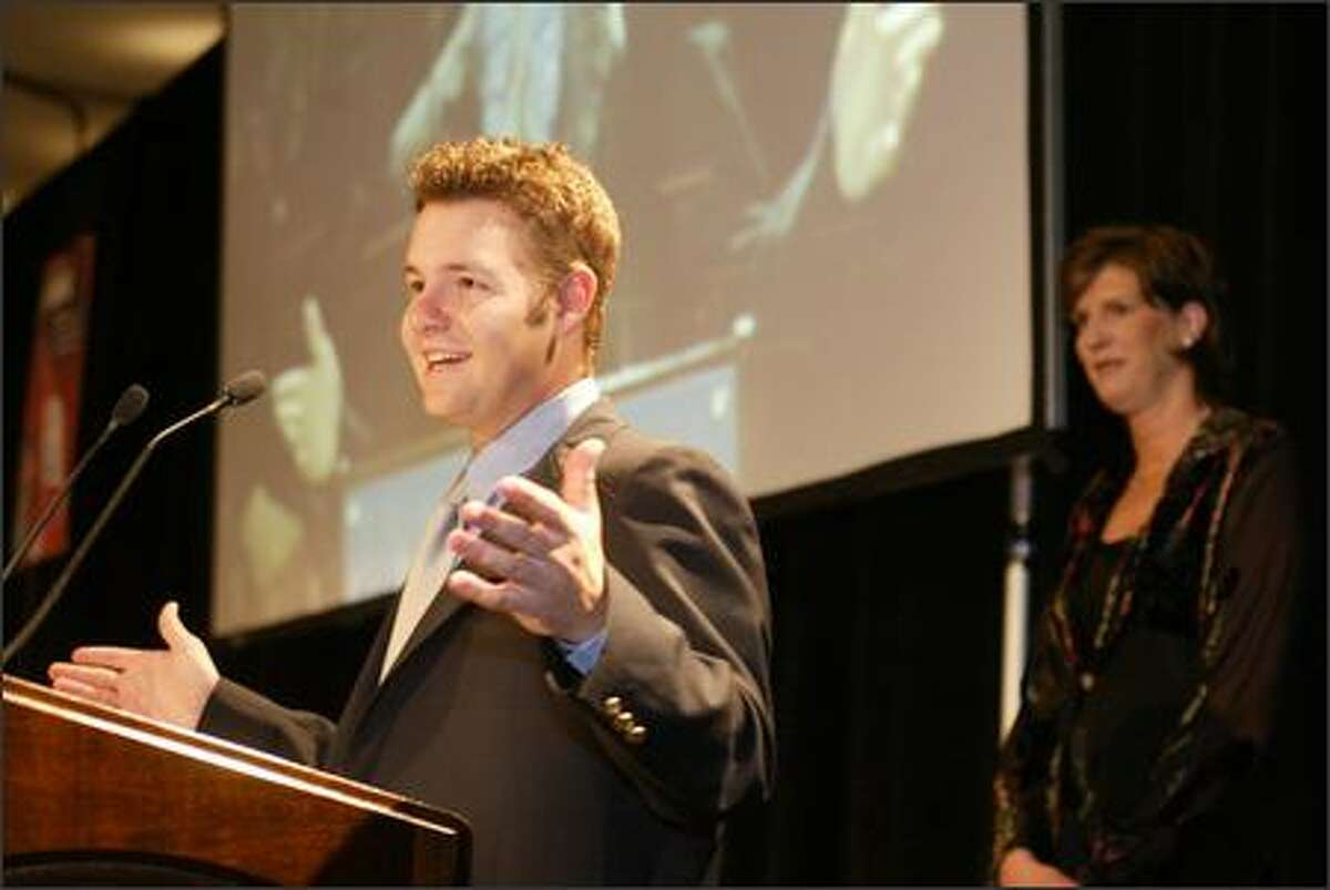 With co-winner Storm coach Anne Donovan in the background, golfer Ryan Moore (right) was surprised that he was the winner at the P-I's Sports Star of the Year banquet.