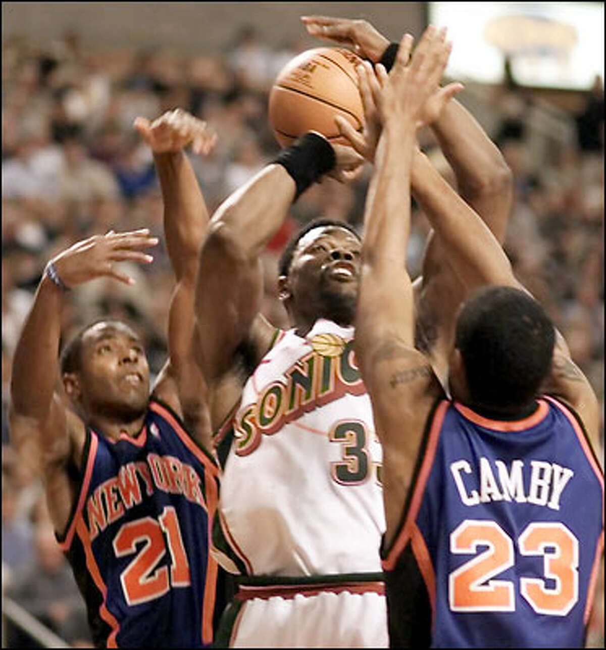 Seattle Supersonics' Patrick Ewing is double teamed by New York Knicks' Charlie Ward and Marcus Camby in the fourthquarter at Key Arena.