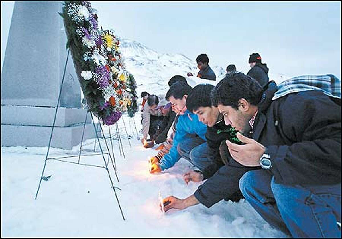 Surviving crew members of the Selendang Ayu place candles in the snow at the Fisherman's Memorial Park in Dutch Harbor, Alaska.