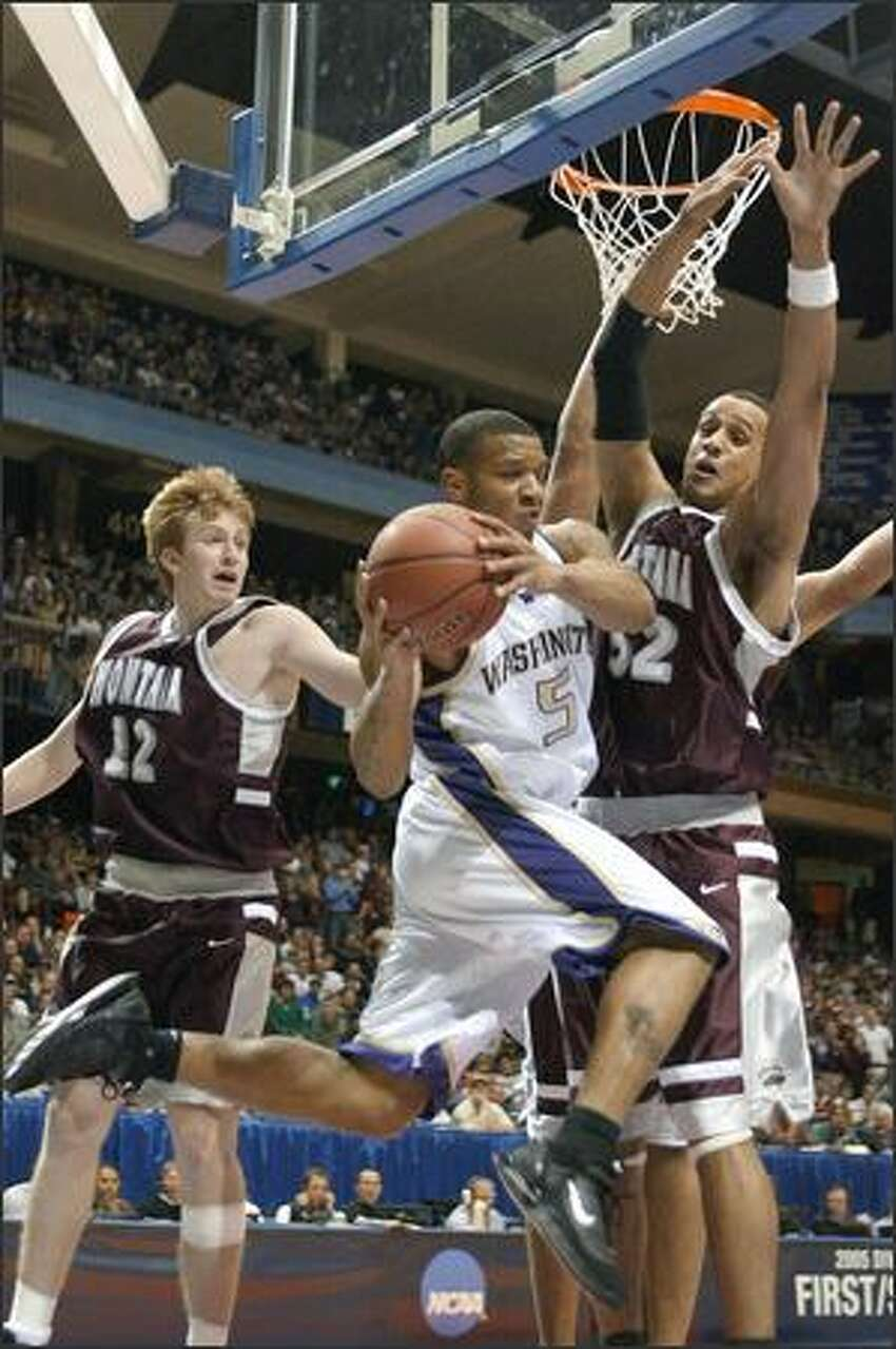 Will Conroy goes underneath the backboard to avoid the defense of Montana's Corey Easley (right) and Kevin Criswell.