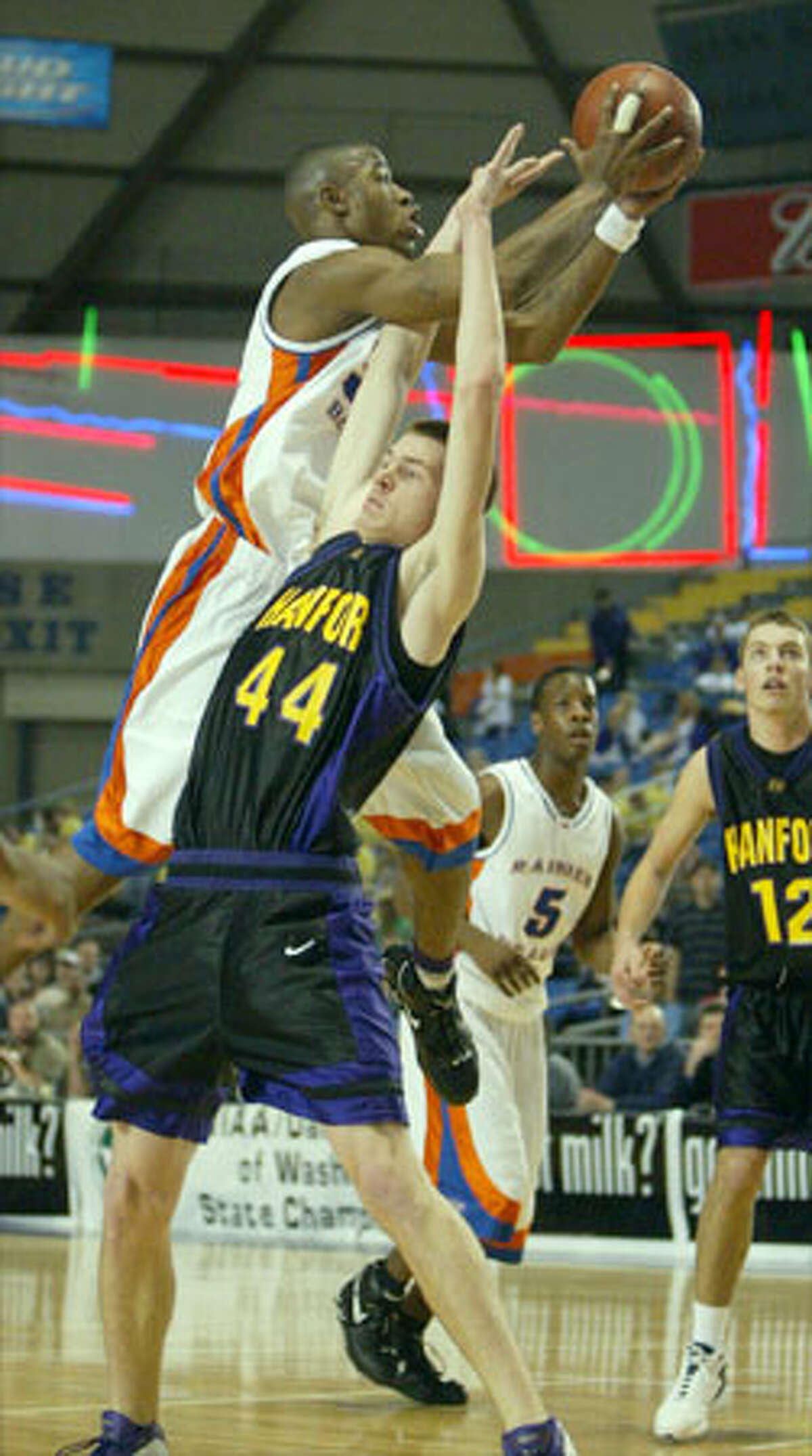Rainier Beach star Terrence Williams goes up and over Hanford's Steve Severin. Williams, who suffered a bloody nose after colliding with a Hanford player, scored 11 points.
