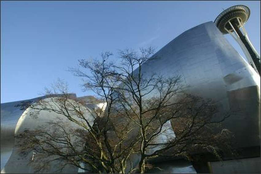 The neighboring Space Needle looms over the Experience Music Project at the Seattle Center.