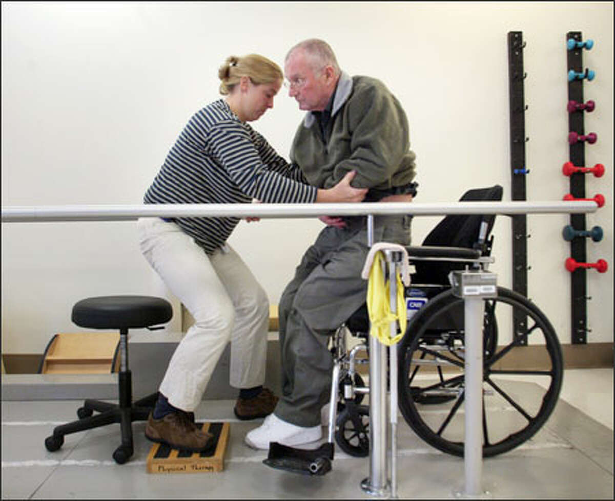 Physical therapist Kristin Kaupang helps Gen. John Shalikashvili out of his wheelchair at Harborview, considered a top center for stroke health.