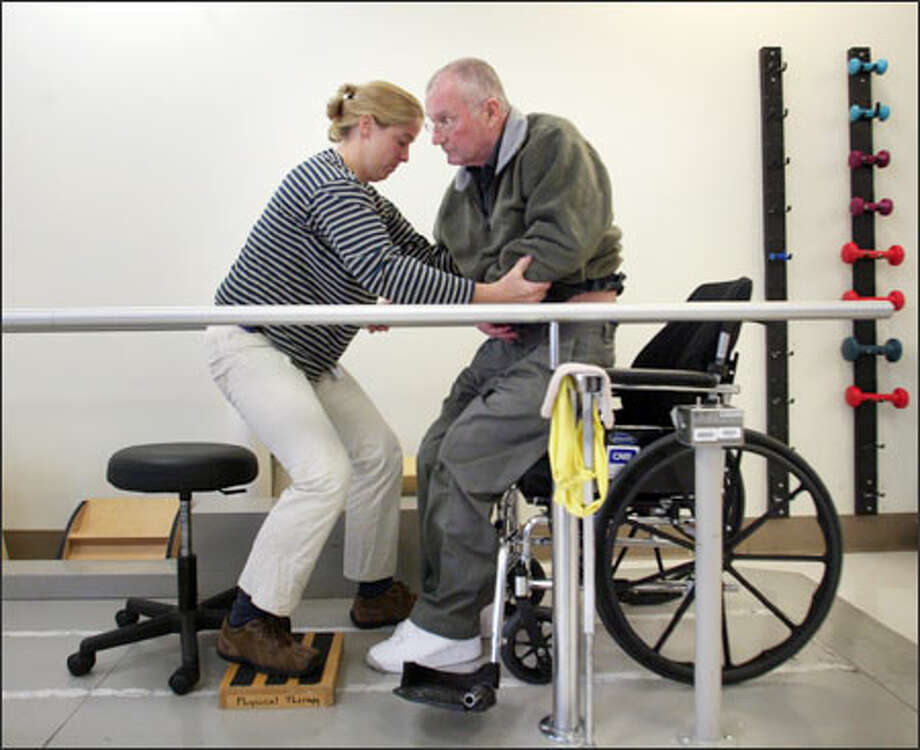 Physical therapist Kristin Kaupang helps Gen. John Shalikashvili out of his wheelchair at Harborview, considered a top center for stroke health. Photo: Dan DeLong/Seattle Post-Intelligencer