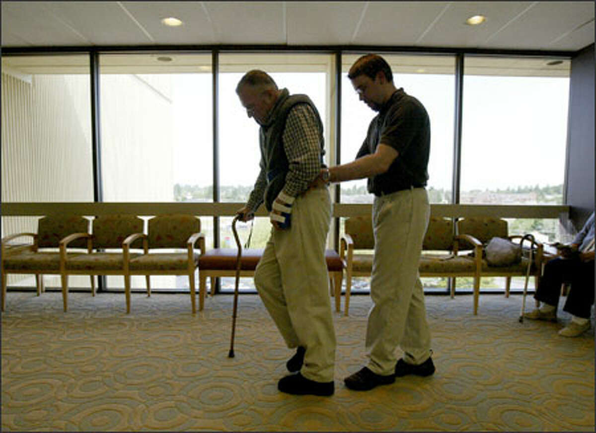 Retired Army Gen. John Shalikashvili, who suffered a major stroke in August, is helped to the elevator by therapist Mike Kubik after a session.