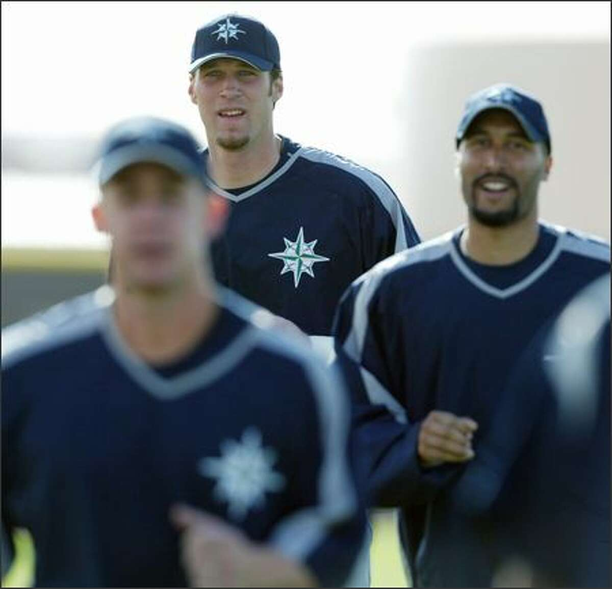 Richie Sexson towers over teammates Bret Boone (foreground) and Randy Winn as they run during the first full-squad workout for the 2005 Seattle Mariners at spring training in Peoria, Ariz. on Tuesday.