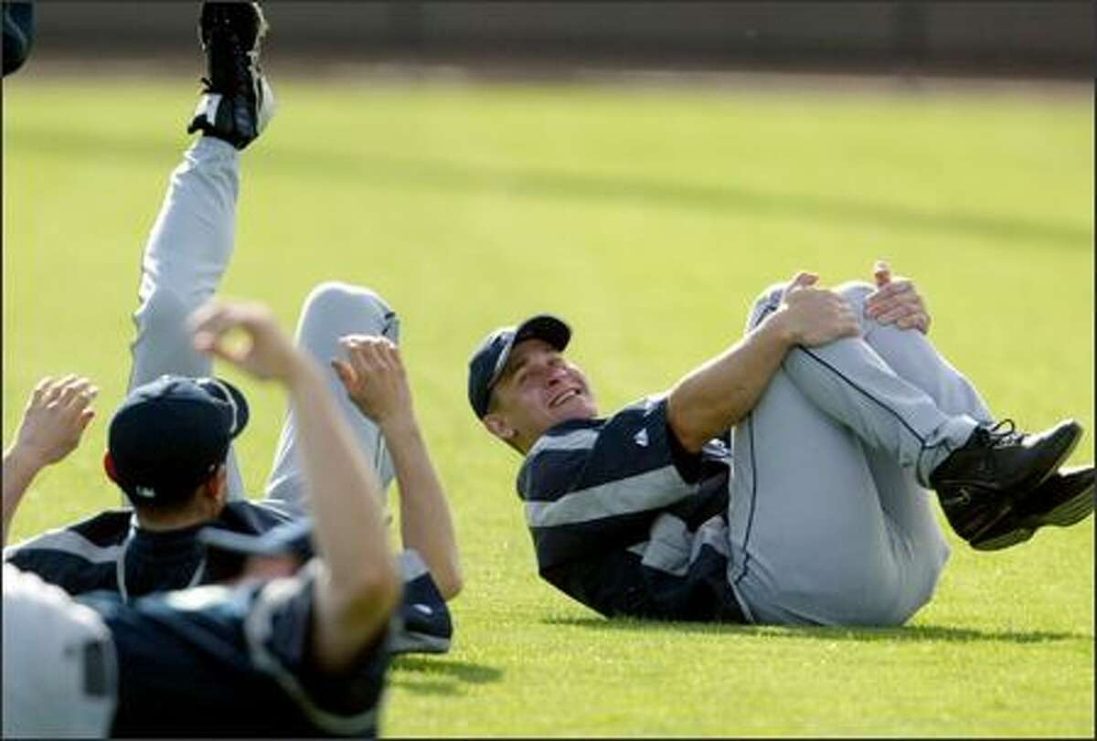 Bret Boone jokes with Ichiro Suzuki while they stretch at the start of the workout.