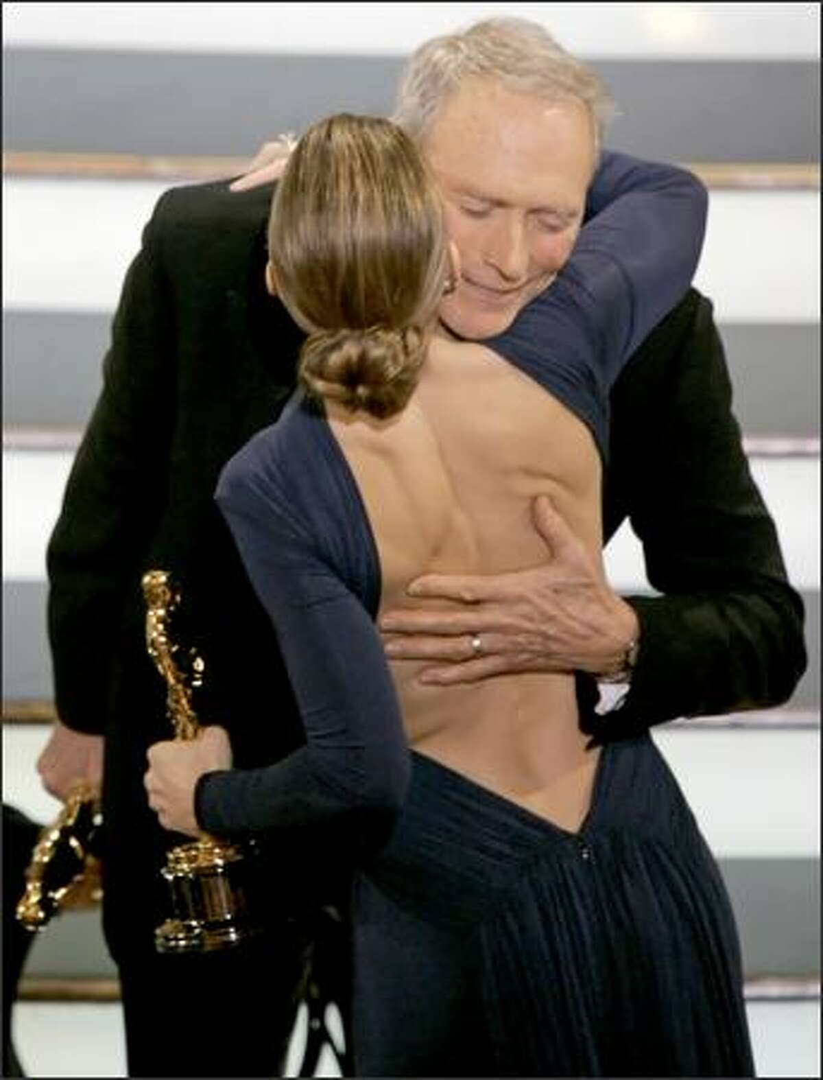 Director Clint Eastwood is congratulated by his film's star, Hilary Swank, before accepting the Oscar for best director for his work on