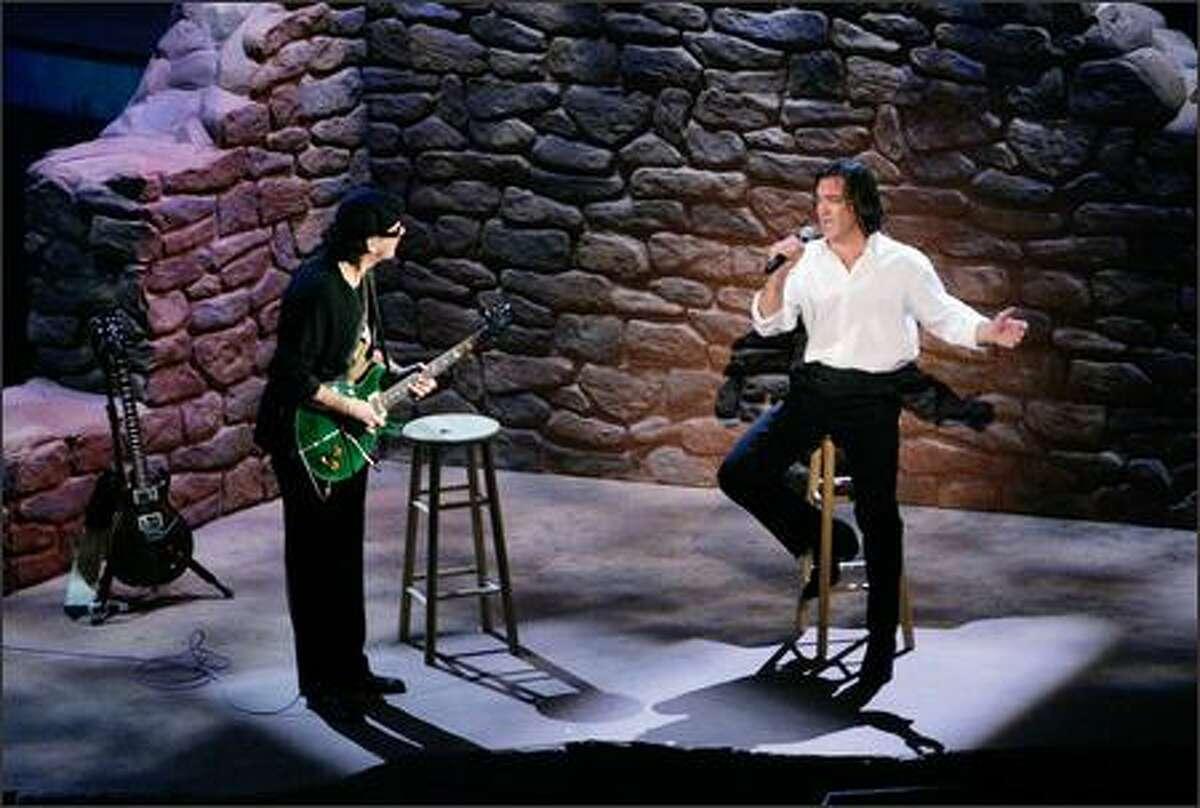 Antonio Banderas, right, and Carlos Santana perform the Oscar-winning best original song