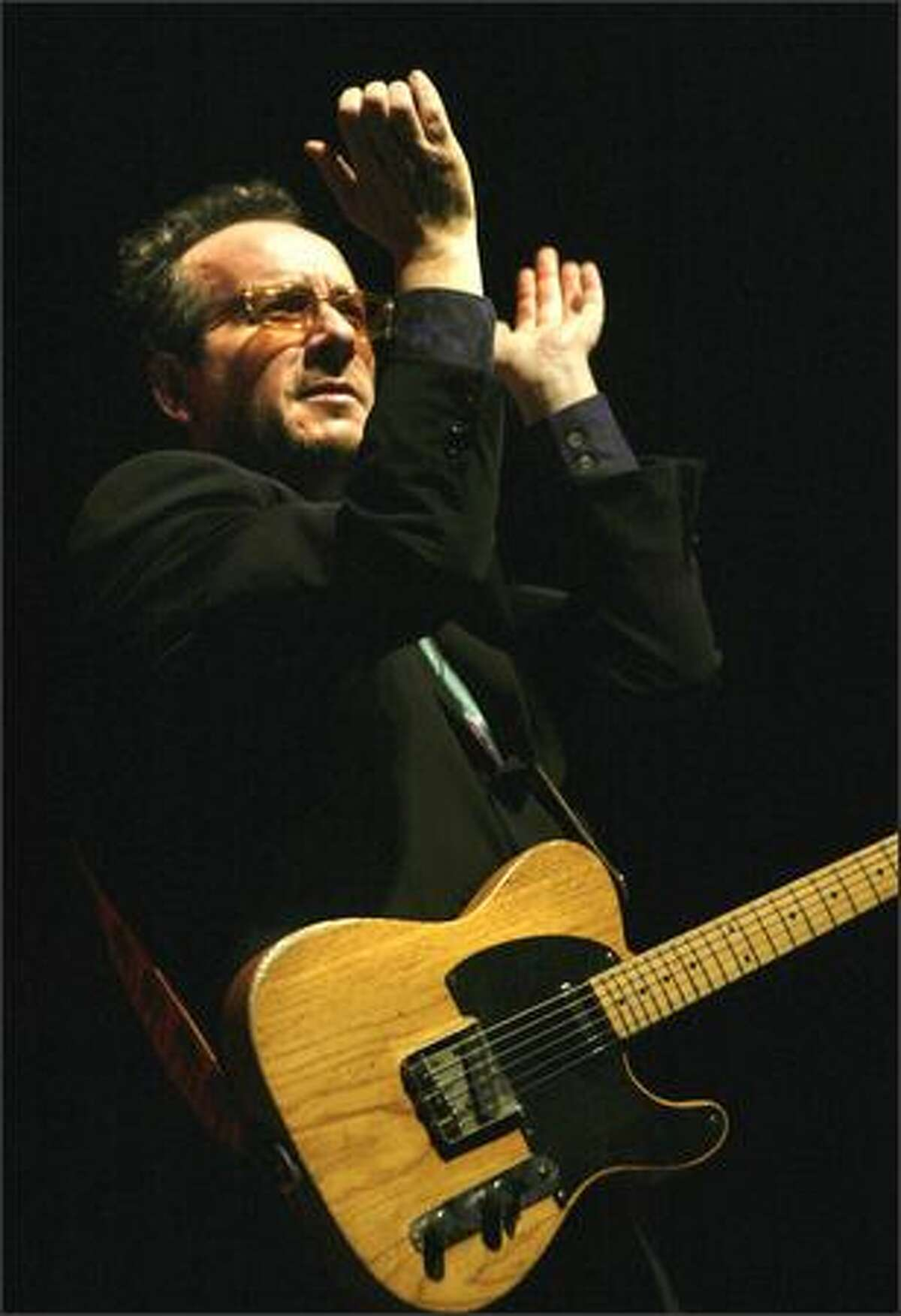 Elvis Costello encourages the audience to clap to the beat as he plays the Paramount Theatre.