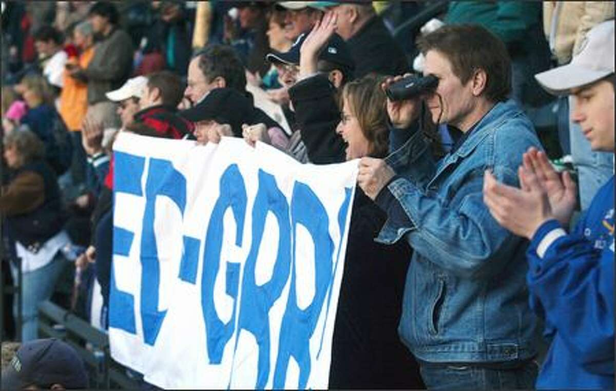 Fans of retired Mariner Edgar Martinez cheer and wave as Martinez throws out the first pitch on opening day of the Mariner's 2005 season.