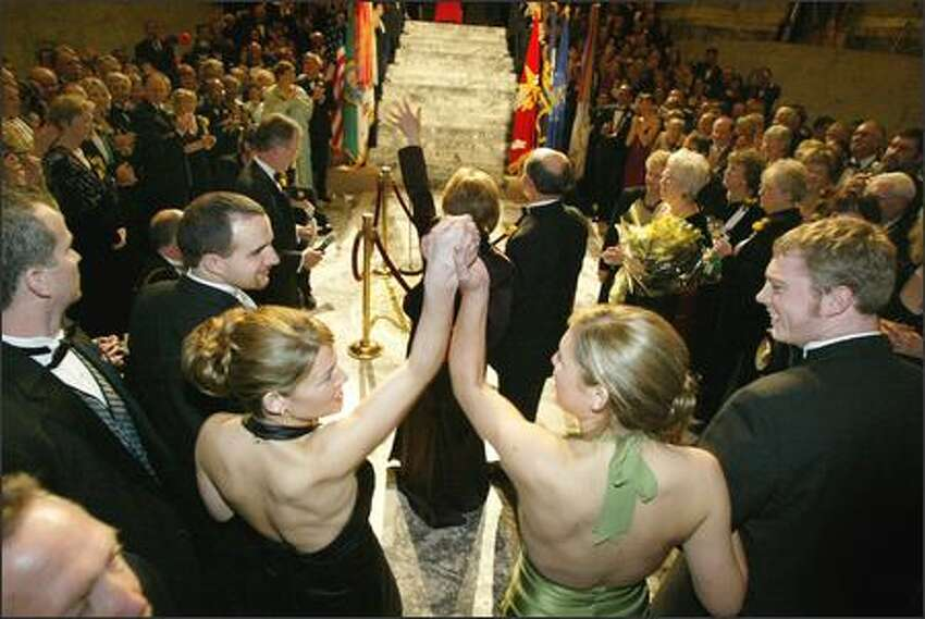 The governor's daughters, Courtney, 25, left, and Michelle, 20, raise their arms in victory as their mother is presented at the Governor's Inaugural Ball in January. Hundreds of people crowded into the Capitol rotunda in Olympia to celebrate the election of Gregoire, who was raised by a single mother and was the first in her family to attend college. Courtney is in her final year of law school, and Michelle is a sophomore in college.