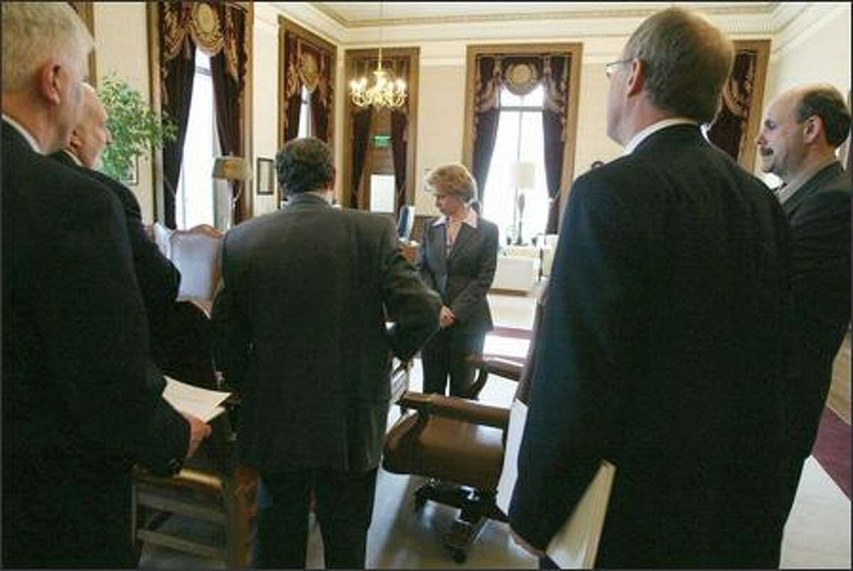 Governor Christine Gregoire is surrounded by budget advisors in her office after announcing her 2005-2007 budget to the press on March 21, 2005.
