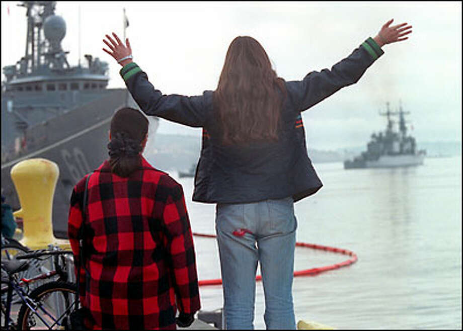 "Ginger Lawrence, 19, waves goodbye to friend Adam Bruce Sinclair, 19, as he leaves aboard the USS Paul F. Foster, at right, for a six-month deployment to the Persian Gulf. Ginger's mom, Rita, left, said: ""It's sad to see such young, beautiful and focused people leave."" Photo: Renee C. Byer, Seattle Post-Intelligencer"