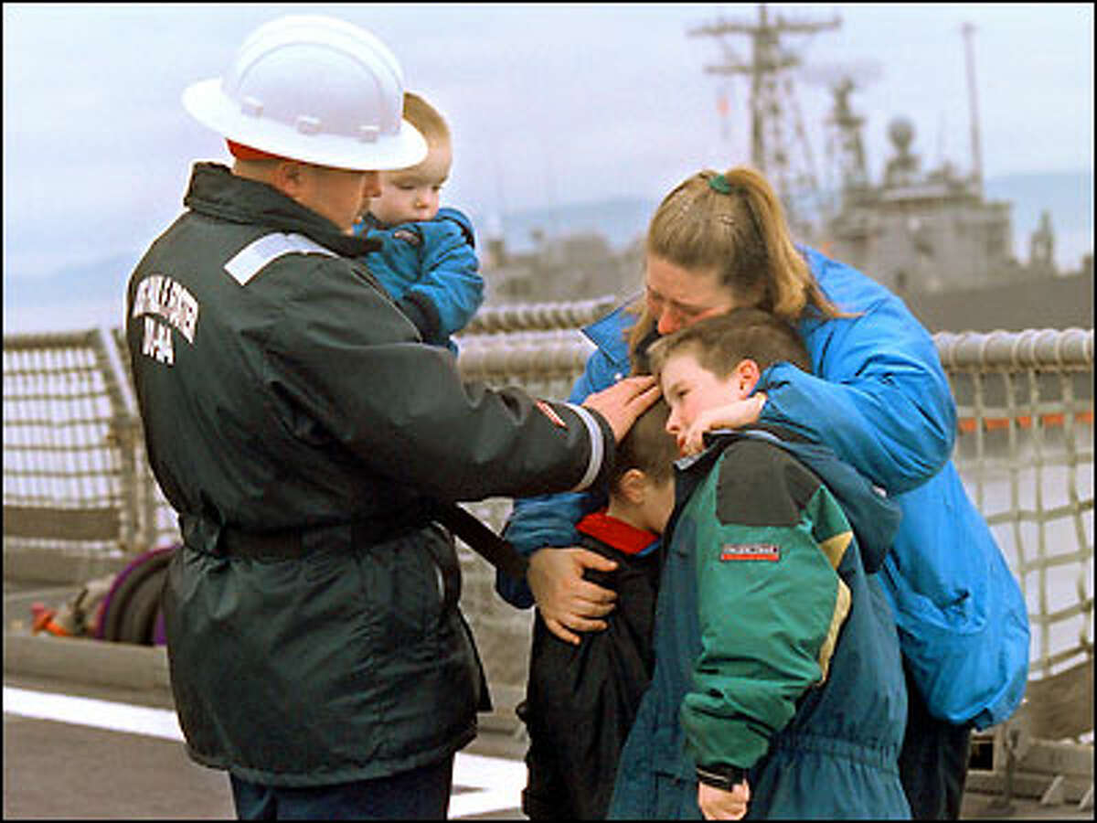Chief Boatswain's Mate Charles Duesler, holding his son Zach, 2, comforts the rest of his family -- Eric, 7; Ronnie, 9; and his wife, Tina -- while saying goodbye in Everett before boarding the ship, the USS Paul F. Foster, for a six-month deployment in the Persian Gulf. Ten years ago, during Operation Desert Storm, virtually all of the state's military bases played a key role.