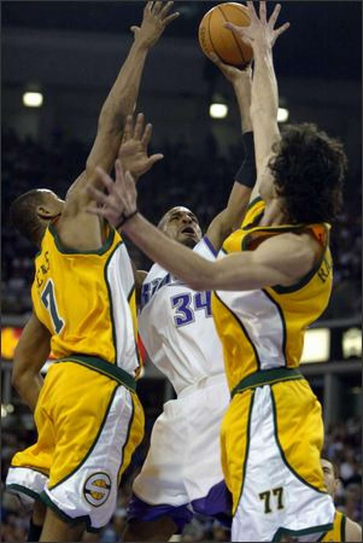 Rashad Lewis and Vladimir Radmanovic put up a block on Sacramento's Corliss Williamson.
