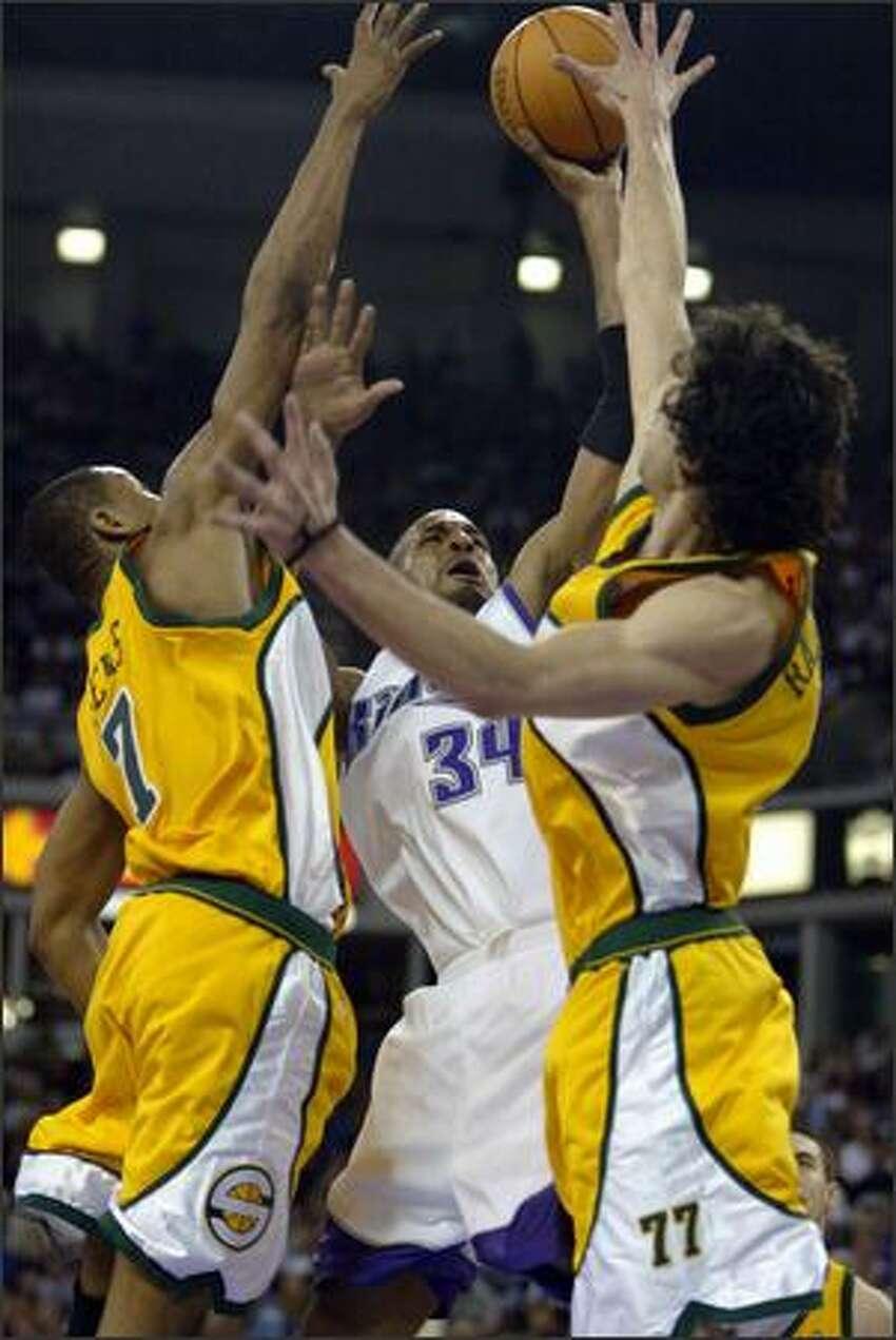 Rashad Lewis and Vladimir Radmanovic put up a block on Sacramento's Corliss Williamson.