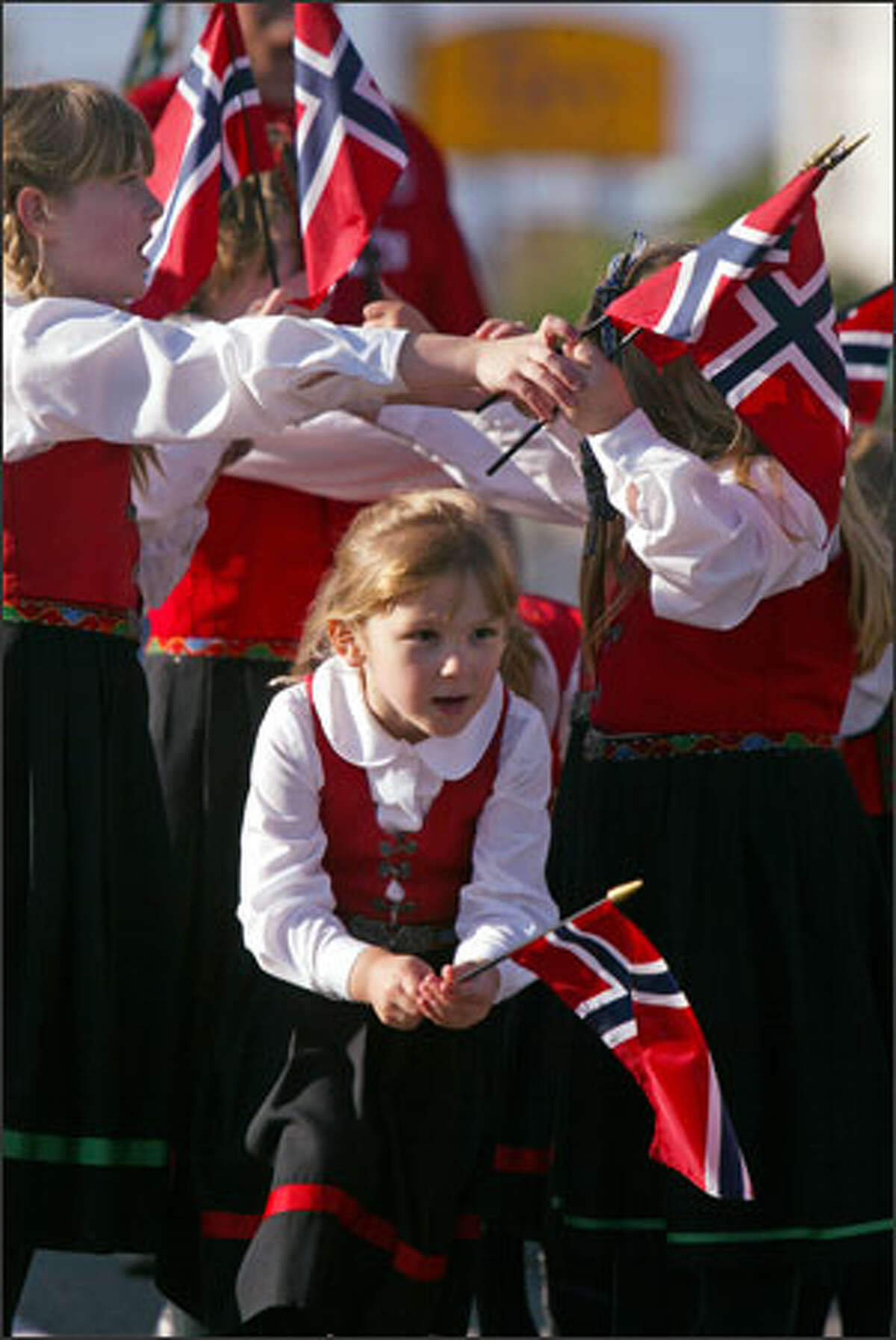 The Young Scandia Dancers from Whidbey Island, bedecked in traditional Scandinavian regalia and holding Norwegian flags, perform in the parade.