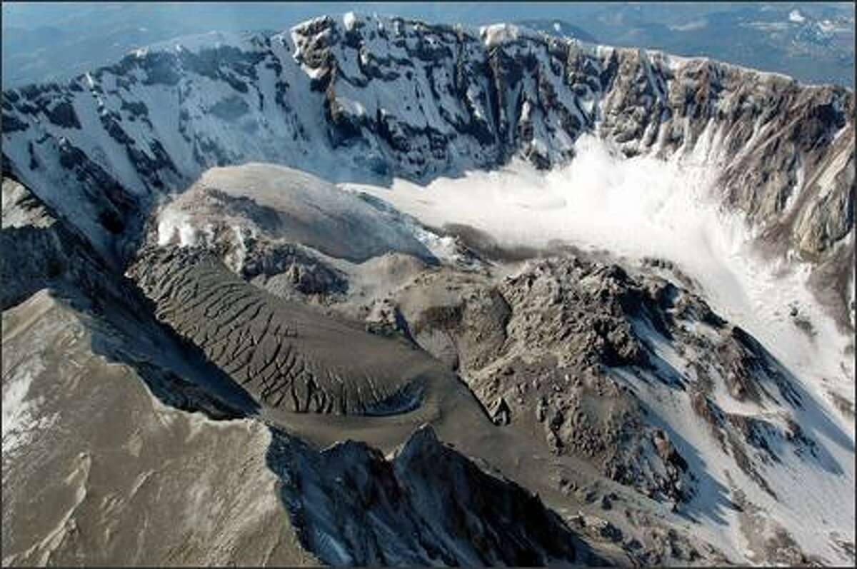 In this March 11, 2005, photo provided by the U.S. Geological Survey Cascades Volcano Observatory, the continually growing new lava dome in the crater of Mount St. Helens continues to dwarf the old lava dome (right). May 18, 2005, marks the 25th anniversary of a massive eruption of the mountain, which began erupting again last October.