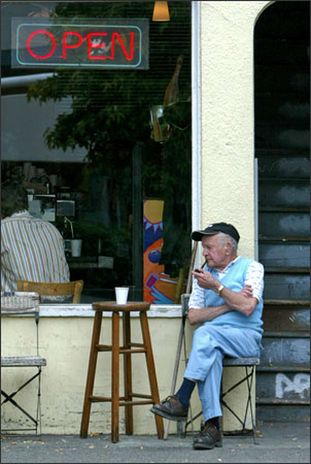 On a recent weekday, John Gouveia, 92, sits outside of Hines Public Market Coffee, an independent shop that's a home away from home for many who work and live in Eastlake, including many artists and writers.