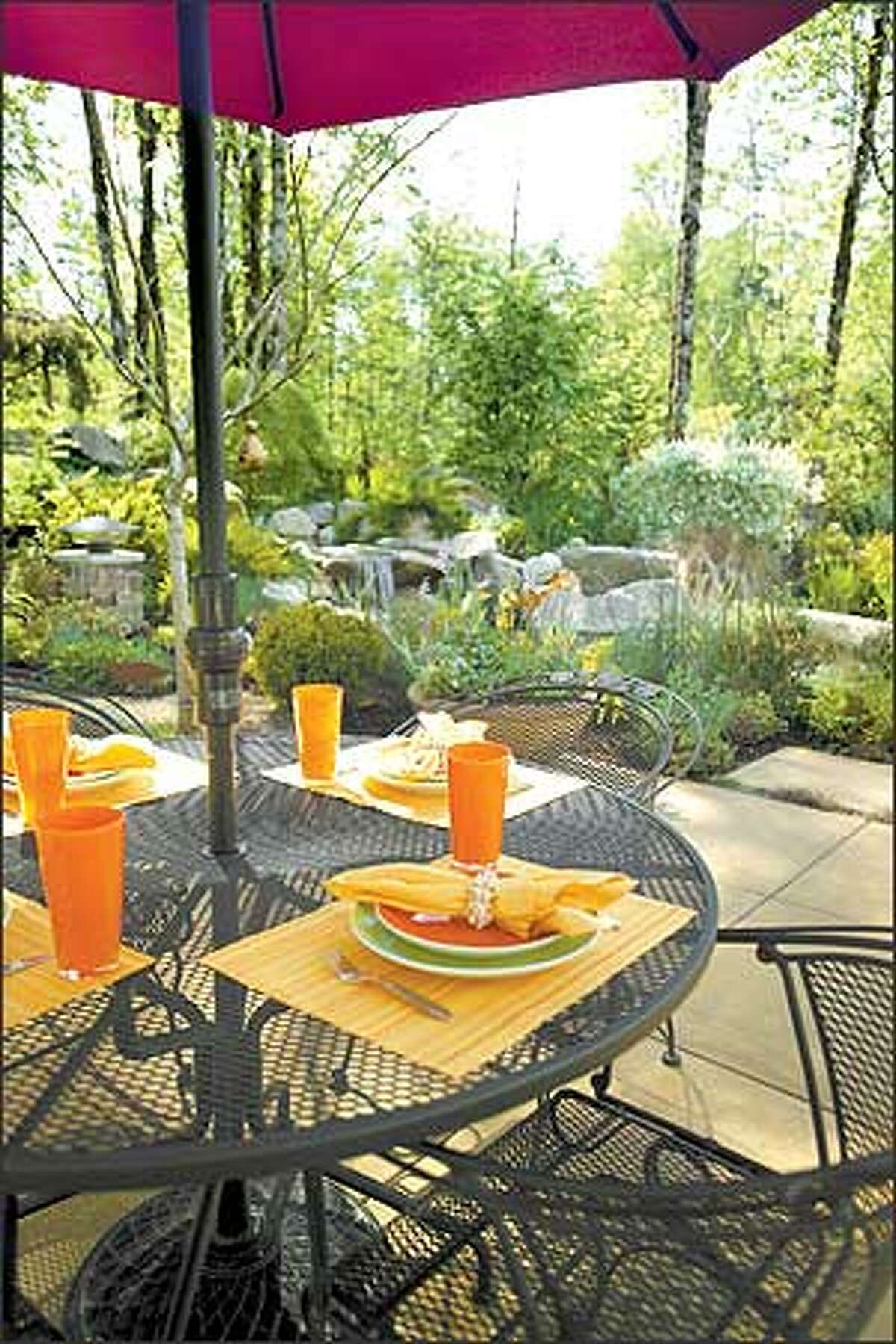 An umbrella-topped wrought-iron dining set allows guests to choose between eating in the sun or shade.