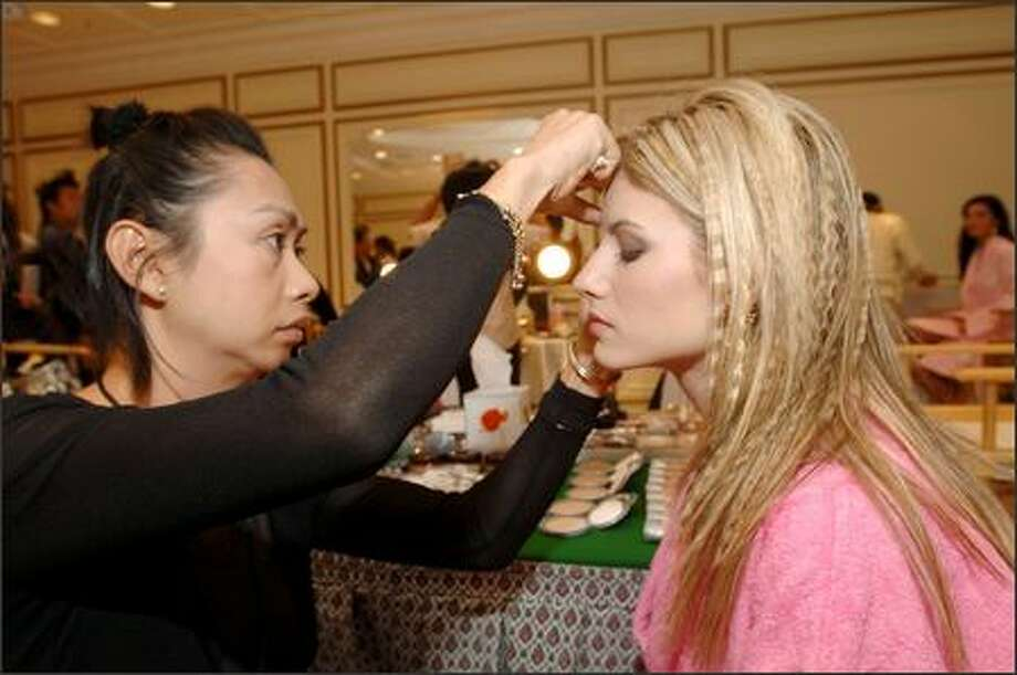 "Makeup artist Sitporn ""Daeng"" Phujaroen applies CoverGirl cosmetics to Evangelia Aravani, Miss Greece, during registration and fittings for the 2005 Miss Universe competition at the Dusit Thani Hotel in Bangkok, Thailand on May 8. The pageant comes to an end May 30 with a live telecast on NBC (tape-delayed in the Pacific time zone). Photo: Miss Universe L.P., LLLP"