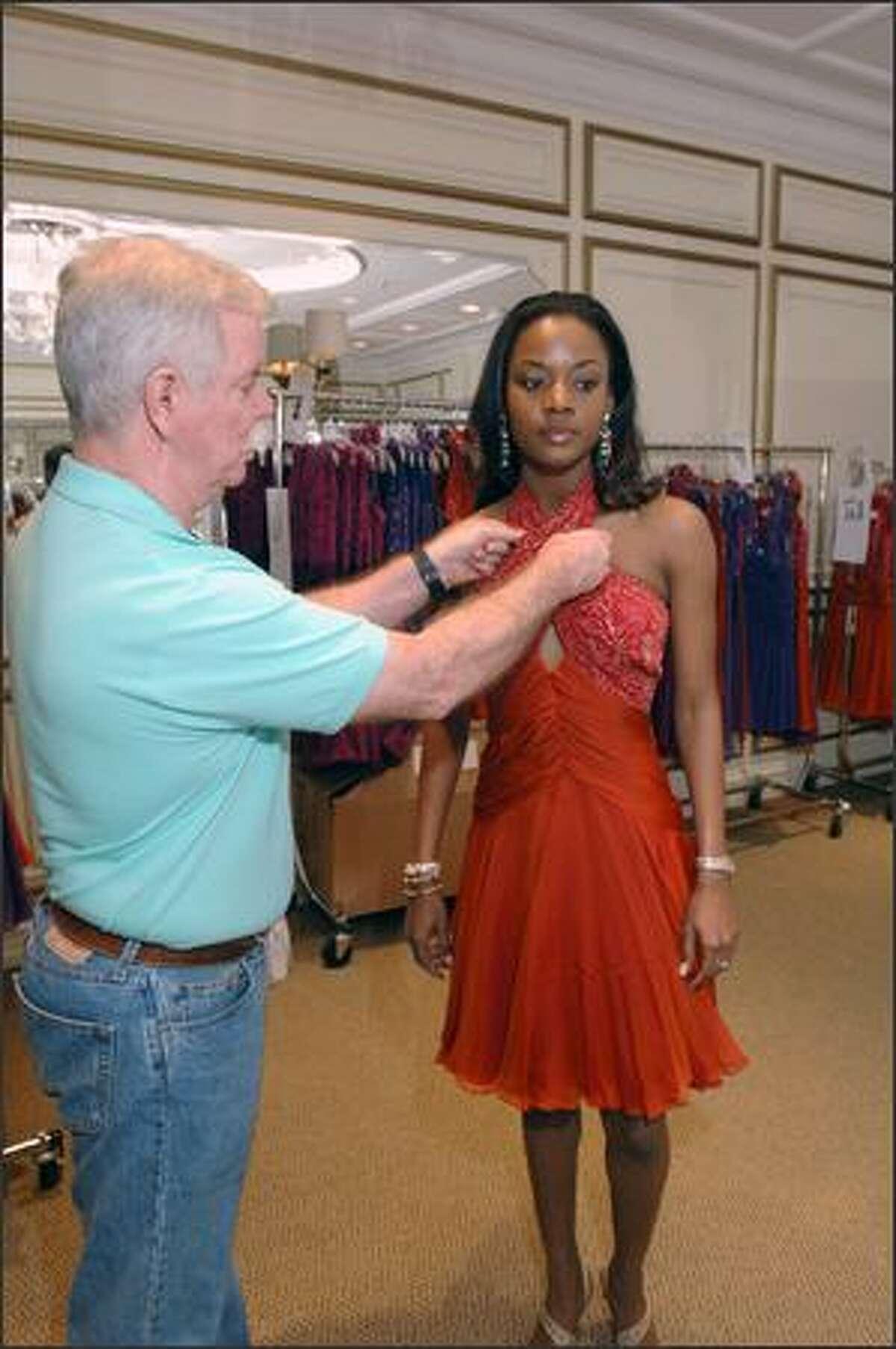 Pete Menefee adjusts a Tadashi dress on Shermain S. Jeremy, Miss Antigua & Barbuda.