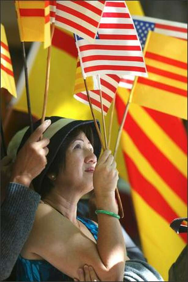 Pre-1975 South Vietnamese flags frame Tam Cong Huyen during protests at the Fairmont Olympic Hotel against Vietnam's prime minister. Photo: Karen Ducey, Seattle Post-Intelligencer