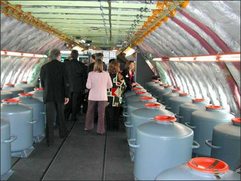 """A group tours the A380's upper deck. Unlike on a Boeing 747, the A380's upper deck runs the length of the plane although it's not as wide as the main deck. Still, it's spacious enough that """"you would never know there are passengers down below,"""" said tour guide Wolfgang Absmeier, an Airbus test pilot. Photo: James Wallace, Seattle Post-Intelligencer"""