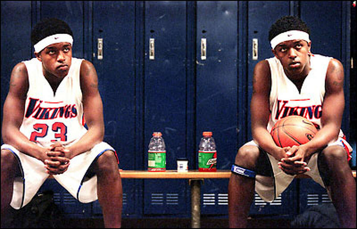Rainier Beach's 6-foot-4 sophmore twins Rodrick and Lodrick Stewart listen intently to their coach before a critical game with Metro League rivals Seattle Prep.