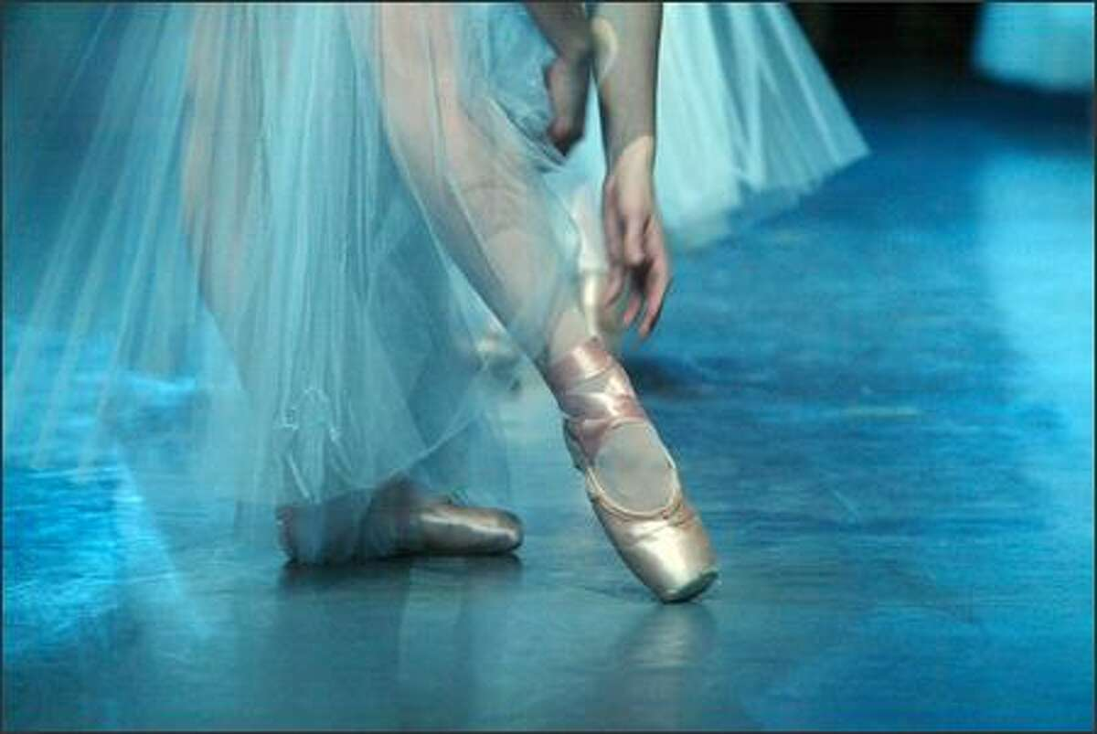 A dancer adjusts her point shoe while waiting for the curtain to open at the start of the Tribute to Kent Stowell and Francia Russell held at McCaw Hall on June 12, 2005.