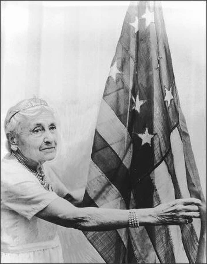 In June 1965 Rosamond Johnson, of Port Orchard, poses with an American flag of 1789 vintage which was used at the inauguration of George Washington.