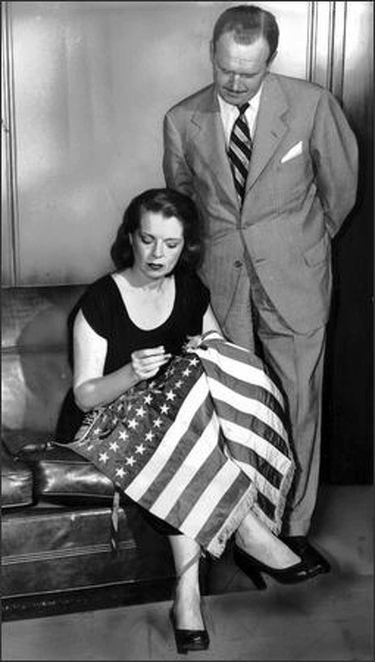 In July 1950, Mrs. Roy Gaston Booker of New York, a descendant of the woman who made the first American flag, puts finishing touches to a new 50-star American flag design favored by an overwhelming majority of newspaper readers polled by Alex Raymond, standing. The extra two stars anticipate Alaska and Hawaii achieving statehood.