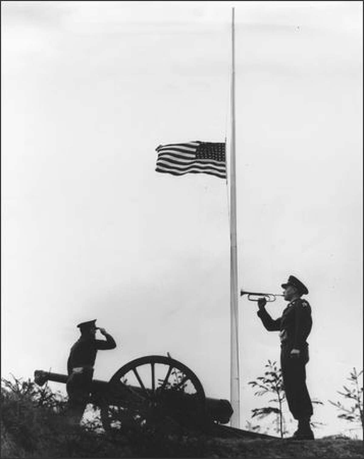 In 1949, Fort Lewis soldiers Sgt. Edgar Enfinger, left, and Pfc. John Richardson observe Armistice Day in solemn and traditional fashion with a salute to the flag.